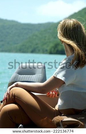 the girl on the boat admires a landscape - stock photo