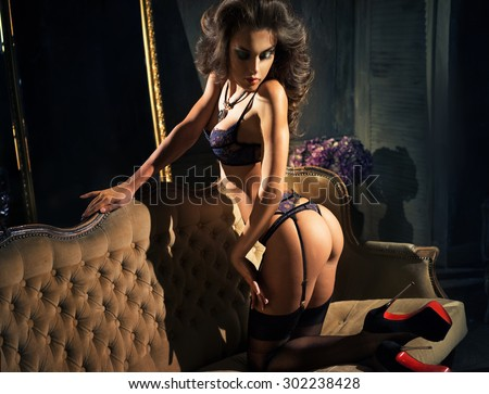 The girl on the couch, wearing shoes and lingerie - stock photo