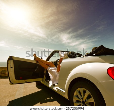 The girl on vacation in a white car - stock photo