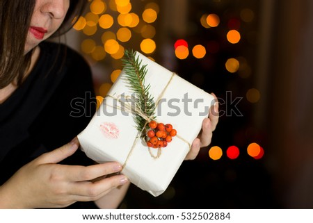The girl packs gifts near a Christmas tree. Christmas Eve.
