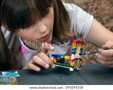 The girl paints a toy chair in different colors. Paints and brush. The chair is painted in all colors of the rainbow