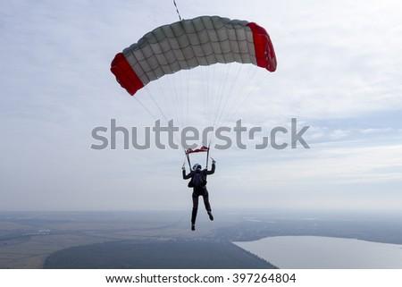 The girl parachutist pilots his parachute. - stock photo