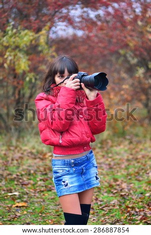 The girl photographs autumnal forest - stock photo