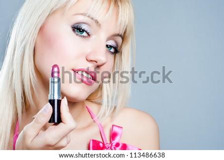 The girl picks up a lipstick - stock photo