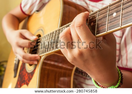 The girl playing guitar in her free time hand focus