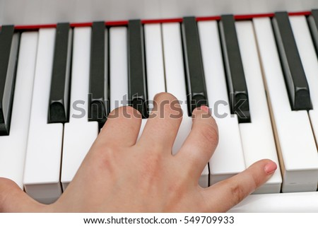 The girl plays piano,close up piano, white and black keyboard