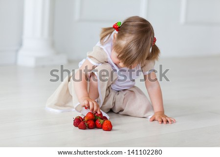 The girl plays with a strawberry on the warm floor