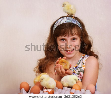 The girl plays with live small chickens