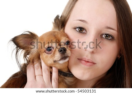 The girl pressed her cheek a little dog. Close-up.