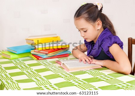 The girl read books behind a table - stock photo