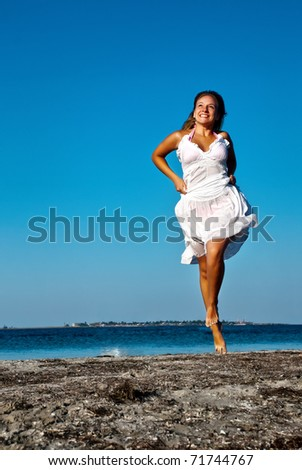 The girl running on seacoast - stock photo