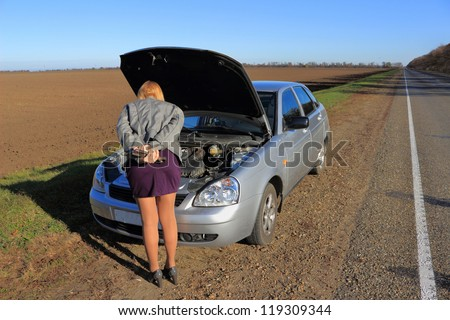 The girl's car broke down on the road - stock photo