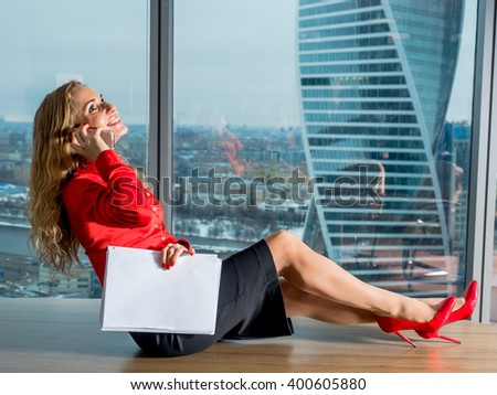 The girl's secretary lying on the table in the office near the panoramic windows with views of Moscow, and talking on the phone - stock photo