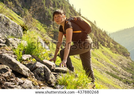 the girl scrambles on the mountain on the background of green grass, spring, Sunny day - stock photo