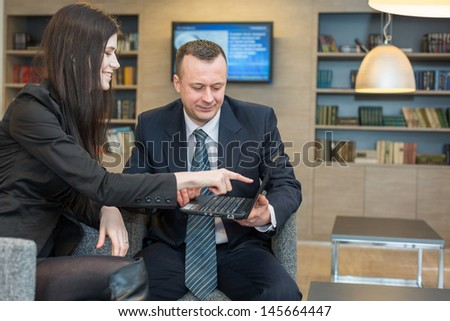 The girl shows a man on a laptop in a business suit, focus on a man.