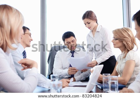 The girl shows the boss of the documents in the office
