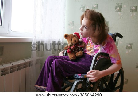 The girl sits in an wheelchair and looks out of the window.