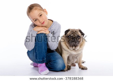The girl sits near a dog on a white background