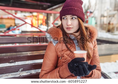 The girl sits on a bench. She has coffee and heats about it hands. It has very interested look. Her hair are developed by wind.