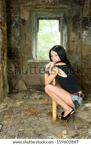 The girl sits with a baseball bat