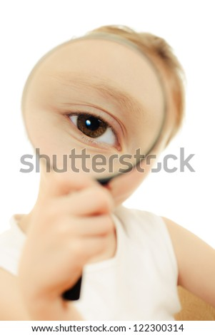 The girl sitting at a table looking through a magnifying glass.