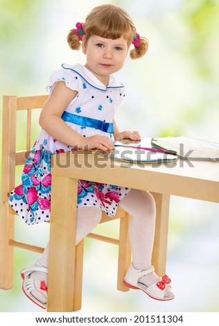 The girl sitting at the table with books.child, happiness and people concept, lovely smiling toddler portrait