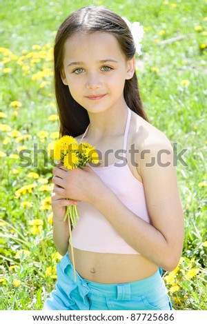 The girl sitting in the grass with dandelion in hand