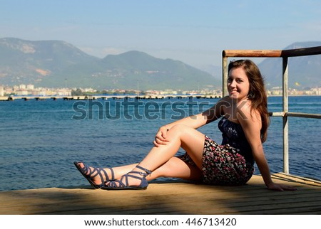The girl sitting on a pier and smiling - stock photo
