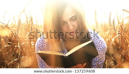 The girl sitting on ripening ears of wheat field on the background of the setting sun, reading a book - stock photo