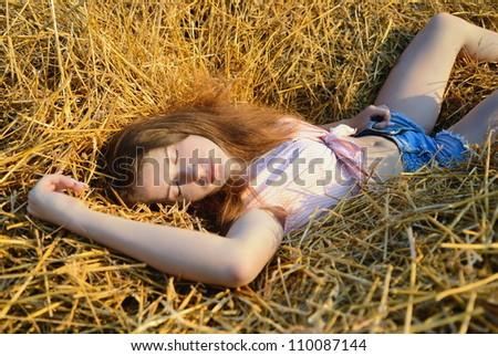 The girl sleeps on a haystack - stock photo