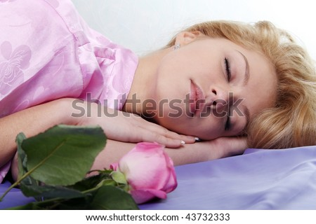 The girl sleeps with a rose on the bed - stock photo