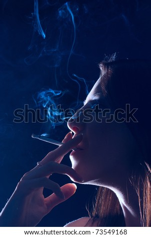 The girl smokes a cigarette on a black background - stock photo