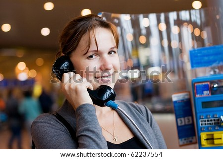 The girl speaks by phone at the airport - stock photo