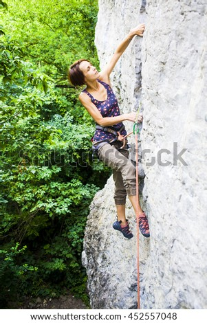 The girl spends time actively engaged in climbing.