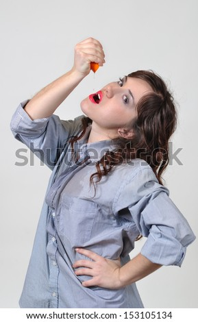 The girl squeezes out juice and drinks it - stock photo