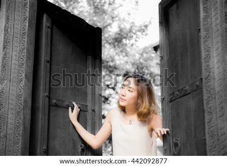 The girl standing next to an old door . soft focus
