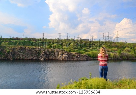 The girl stands near the river and looks at a power line - stock photo