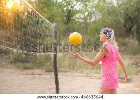 The girl strikes a ball in beach volleyball