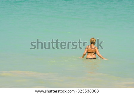 The girl swiming in sea waves. - stock photo