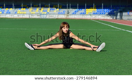 The girl take a stretch on the football field - stock photo