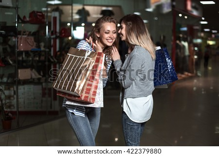 the girl talking to her friend over the ear. Fashion Shopping two ladies Portrait. Beauty Woman with Shopping Bags in Shopping Mall. Shopper. Sales. Shopping Center