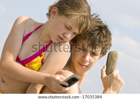 The girl talks by a mobile phone, the guy speaks on the phone from a stone