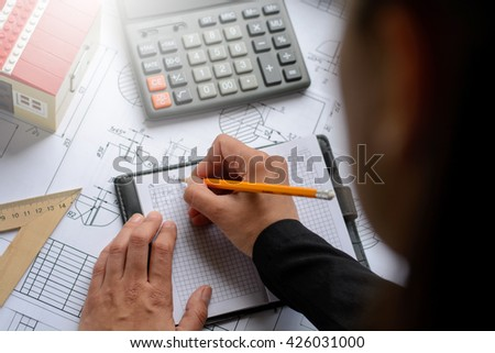 The girl the designer, architect, business woman makes calculations, drawing drawings, diagram, writes the formula on a wooden table with blueprints, toy house and calculator. With lights effects.