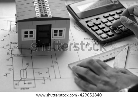The girl the designer, architect, business woman makes calculations, drawing drawings, diagram, writes the formula on a wooden table with blueprints, toy house and calculator. Black and white - stock photo