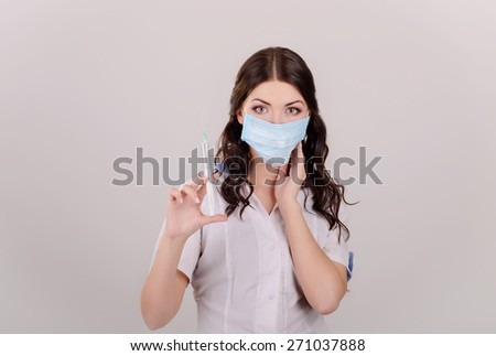 The girl the doctor in a medical mask with a syringe in hands