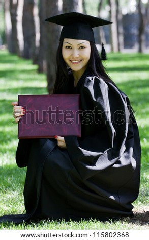 The girl the graduate of university with the diploma in hands, in park - stock photo