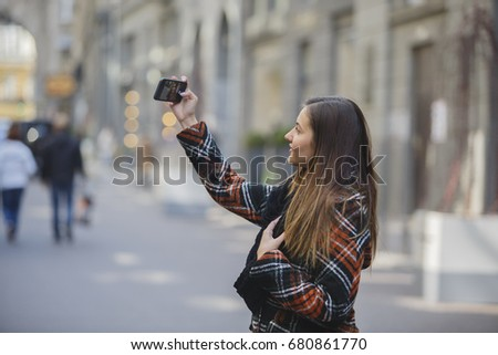 The girl travels and makes selfie in the streets of ancient European city