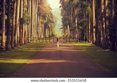 The girl walking down the road surrounded by palm trees to the mountains far away - stock photo