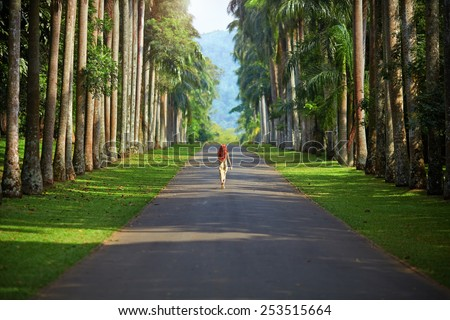 The girl walking down the road surrounded by palm trees to the mountains far away