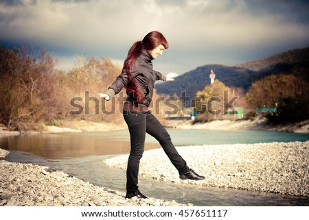 the girl walks across the river on a background of mountains in the cold season